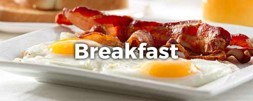Eggs and bacon on a plate with the word Breakfast written on top